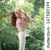 Portrait of a beautiful mother holding cute baby in the park - stock photo