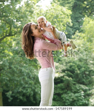 Portrait of a beautiful mother holding cute baby in the park