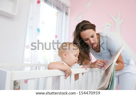 Portrait of a beautiful mother teaching toddler to read from book - stock photo