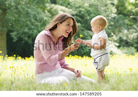 Portrait of a beautiful mother with baby playing in the park - stock photo