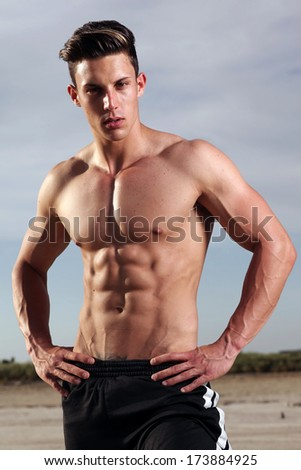 portrait of a beautiful muscular male model in black briefs in provocative pose outdoors  - stock photo
