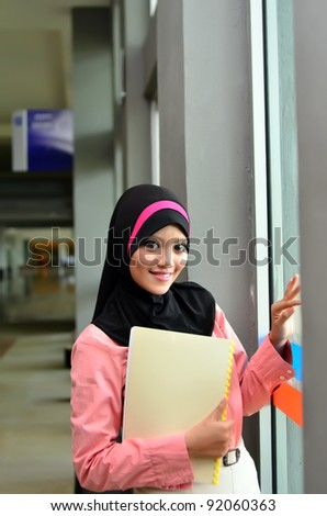 Portrait of a beautiful Muslim woman holding a file and smile