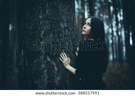 Portrait of a beautiful mysterious woman in the forest. Cold ton - stock photo