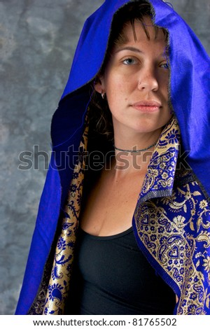 Portrait of a beautiful mystical woman looking at viewer her head is covered with blue hood. - stock photo