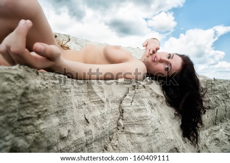 Portrait of a beautiful naked woman laying on sand coast with seaweed - stock photo