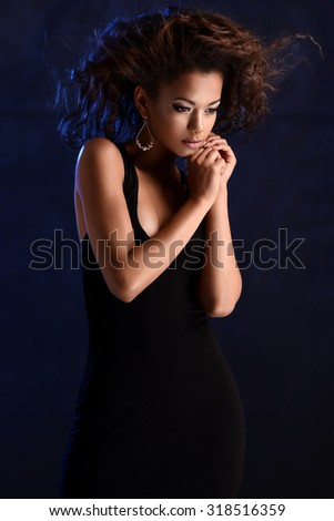 Portrait of a beautiful natural young African woman with afro. Elegant woman on colorful background