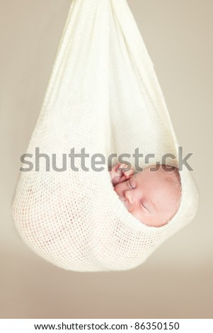 Portrait of a beautiful newborn baby sleeping in a hammock - stock photo