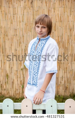 Portrait of a beautiful of Ukrainian little boy posing in traditional shirt