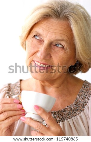 portrait of a beautiful old woman drinking coffee