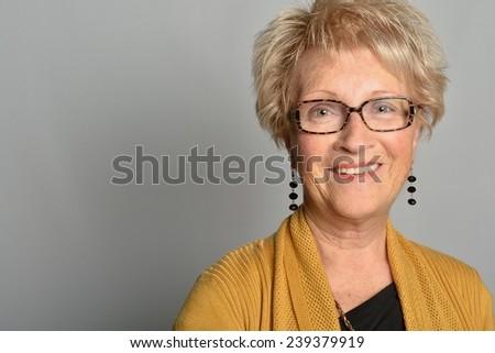portrait of a beautiful old woman with beautiful smile, sparkling eyes, 70, wearing glasses and a yellow cardigan - stock photo