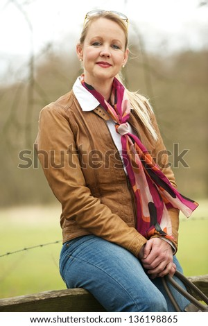 Portrait of a beautiful older woman sitting outdoors - stock photo