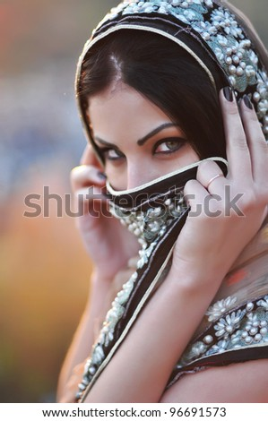 Portrait of a beautiful oriental  woman covered with a colorful veil - stock photo