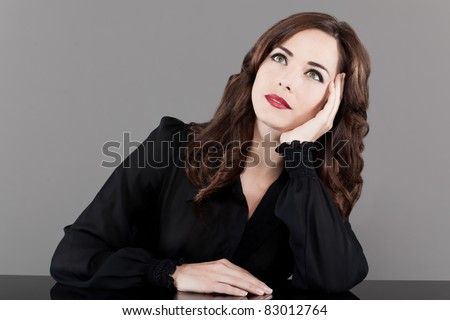 Portrait of a beautiful pensive middle aged woman looking up on gray background - stock photo
