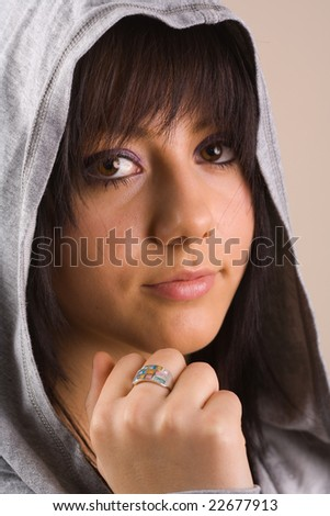 Portrait of a beautiful pensive teenager with sweater and hood - stock photo