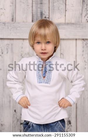 Portrait of a beautiful piercing gaze of Ukrainian little boy. Boy in with blue eyes posing in traditional shirt. - stock photo