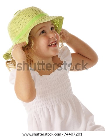 Portrait of a beautiful preschooler trying on a spring green Easter bonnet. - stock photo