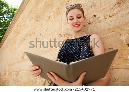 Portrait of a beautiful professional business woman holding and reading a work diary while leaning on an old stone building wall in a classic city, outdoors. Smart professional young woman smiling. - stock photo