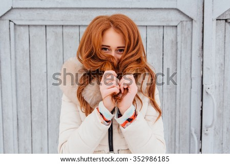 Portrait of a beautiful red hair young woman in warm clothes outdoor on the grey wooden background. Girl shows different emotions. - stock photo