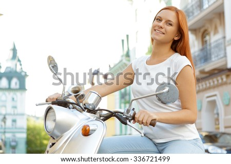 Portrait of a beautiful red-haired girl wearing white shirt, sitting on a silver retro scooter, smiling and looking at the camera, European city on a background - stock photo