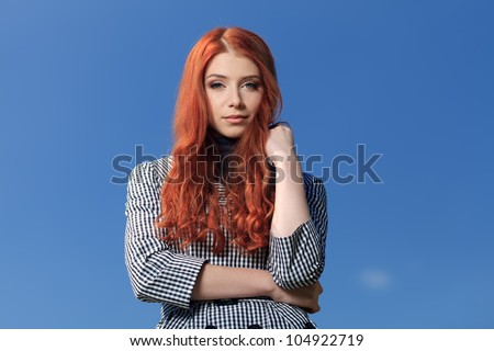 Portrait of a beautiful red-haired young woman over blue sky. - stock photo