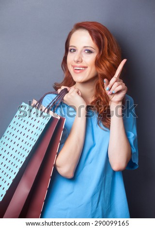 Portrait of a beautiful redhead girl in blue dress with shopping bags on grey background