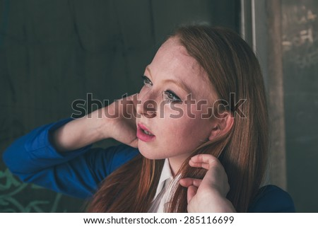 Portrait of a beautiful redhead girl in blue jacket posing in an urban context - stock photo
