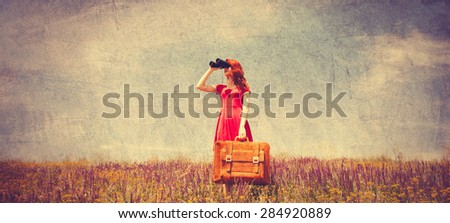 Portrait of a beautiful redhead girl in red dress with suitcase and binocular on the meadow. Photo in old color image style - stock photo