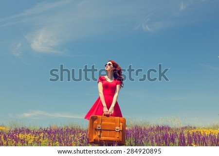 Portrait of a beautiful redhead girl in red dress with suitcase on the meadow.  - stock photo