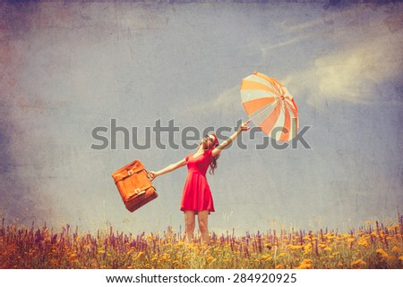 Portrait of a beautiful redhead girl in red dress with umbrella and suitcase on the meadow. Photo in old color image style. - stock photo