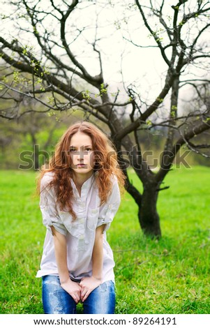 Portrait of a beautiful redhead girl in spring garden - stock photo
