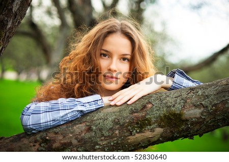 portrait of a beautiful redhead girl in the spring garden - stock photo