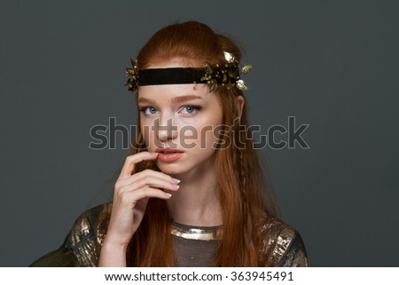 Portrait of a beautiful redhead woman in trendy cloth posing over gray background - stock photo