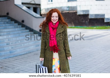 Portrait of a beautiful redhead woman is standing near the stairs and cute angry, eyes closed, green coat, pink scarf, shopping bag in hand outdoor, spring - stock photo