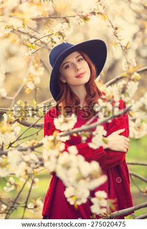 Portrait of a beautiful redhead women in red sweater and hat in blossom apple tree garden in spring time on sunset. - stock photo