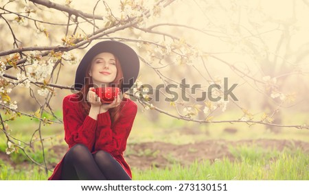 Portrait of a beautiful redhead women in red sweater and hat with cup in blossom apple tree garden in spring time on sunset. - stock photo