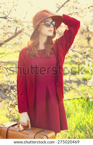 Portrait of a beautiful redhead women in red sweater and hat with suitcase in blossom apple tree garden in spring time on sunset. - stock photo