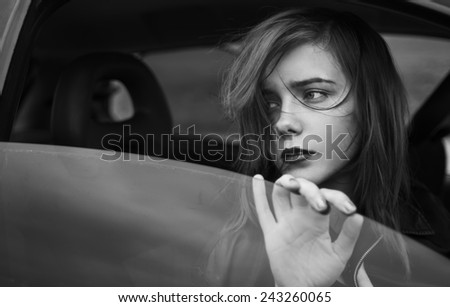 portrait of a beautiful sad girl in the car - stock photo