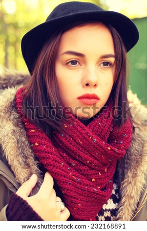 Portrait of a beautiful sad hipster girl in a hat.and a scarf. Outdoors, lifestyle.