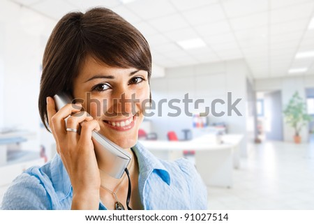 Portrait of a beautiful secretary in an office environment - stock photo