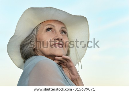 Portrait of a beautiful senior woman on a background of  sky - stock photo