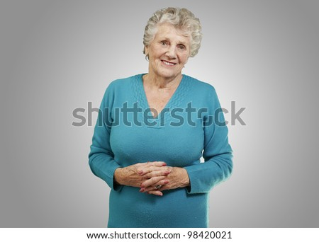 portrait of a beautiful senior woman smiling against a grey background - stock photo