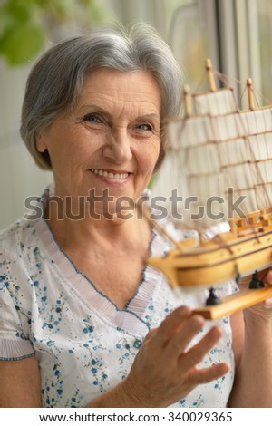 Portrait of a beautiful senior woman with miniature ship