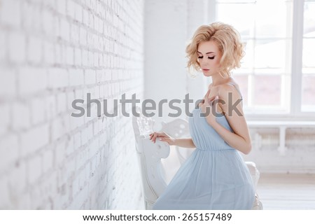 Portrait of a beautiful sensual and sexy blonde girl in a blue dress sitting on a chair against a white brick wall in the Studio - stock photo
