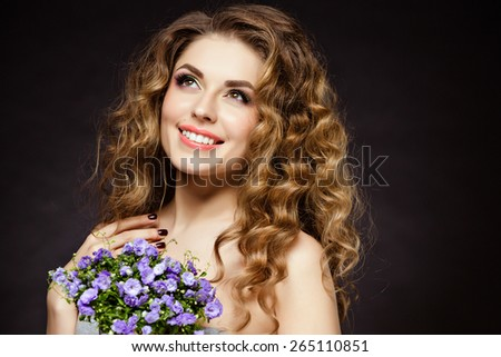 Portrait of a beautiful sensual brunette girl with flowers in their hands, smiling happily in the Studio on a dark background - stock photo