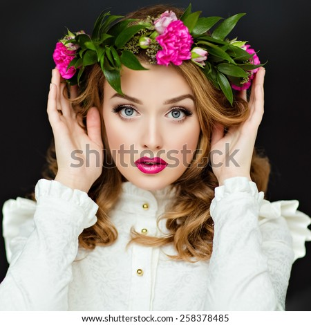 Portrait of a beautiful sensual glamorous yellow-haired girl in a white blouse with a wreath of flowers on his head, in the Studio on a dark background, close up - stock photo