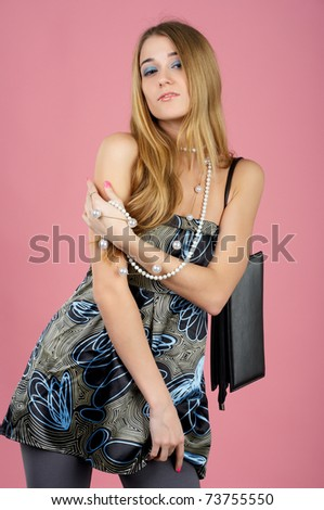 Portrait of a beautiful sensual woman with handbag against pink background - stock photo