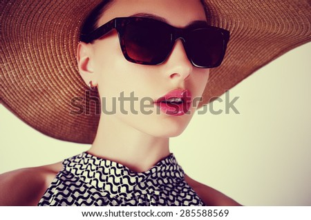 Portrait of a beautiful sensual young brunette woman in a hat and sunglasses - stock photo