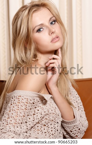 Portrait of a beautiful sensuality young woman with long blonde hair wearing a sweater