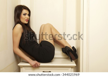 Portrait of a beautiful sexy and attractive young adult brunette sensuality pretty woman posing in black dress in vintage retro style apartment - stock photo