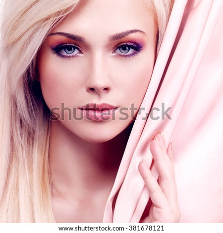 Portrait of a beautiful sexy tender woman with pink silk posing at studio isolated on white. - stock photo